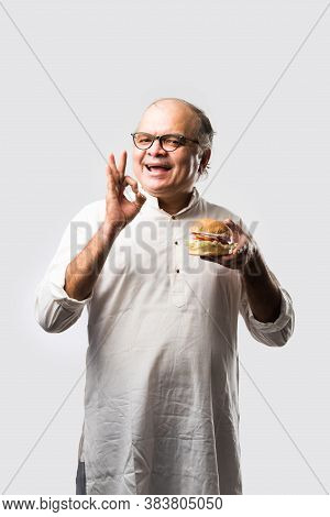 Happy Indian Senior Man Eating Burger Or Hamburger With Cold Drink