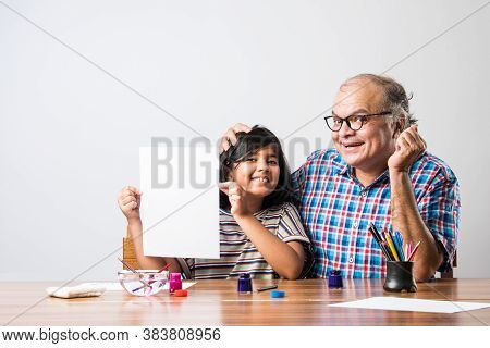 Indian Grandfather Helping Grand Daughter Drawing & Painting With Colours And Brush On Paper At Home