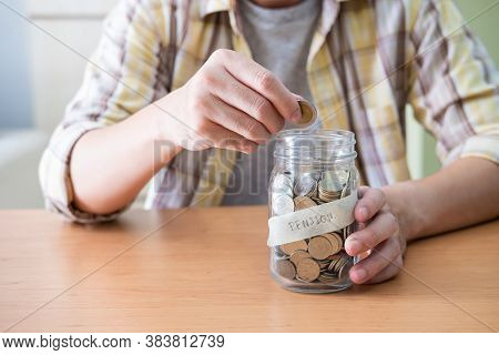 Selective Focus At The Glass Jar. Men Hand Putting Coin Into Glass Jar Full Of Coin Saving For Retir