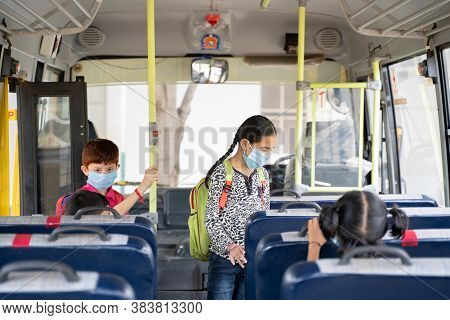 Kids With Medical Mask Coming Inside School Bus And Sitting On Seats While Maintaining Social Distan