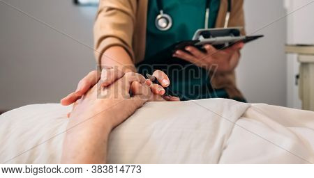 Unrecognizable Young Female Doctor Comforting Unrecognizable Older Female Patient