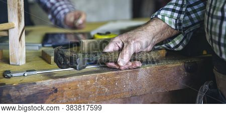 Detail Of Carpenters Hand Holding A Hammer Leaning On The Workbench