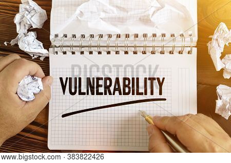 Business And Finance Concept. A Man Writes Text - Vulnerability In A Notebook . Around A Notepad And