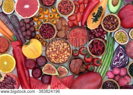 Plant based health food high in lycopene with fruit & vegetables high in antioxidants, anthocyanins, vitamins, carotonoids, minerals, vitamins & dietary fibre. Vegan health care concept. Flat lay.