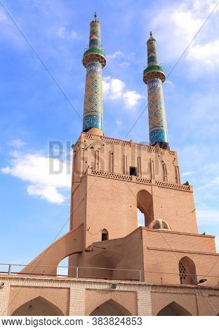 Back side of main entrance and minarets of Grand Jame Mosque (Masjid-e Jameh Mosque, Friday Mosque) in Yazd, Iran. The text on the tower is a quote from the Quran