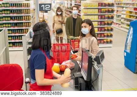Customers in supermarket checkout queue wearing masks and following social distancing rule during Covid-19 quarantine time