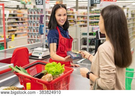 Young woman with long hair standing in front of cashier paying for goods in modern supermarket with bank card