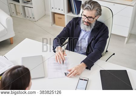 High angle view shot of professional HR manager sitting in front of unrecognizable applicant looking through CV and asking questions