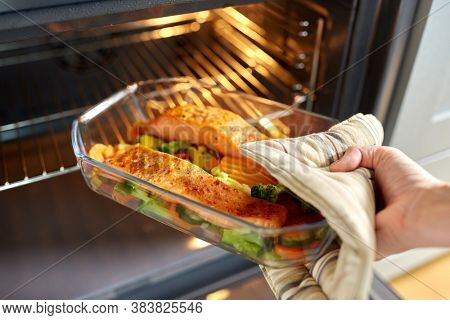 food cooking, culinary and people concept - young woman with potholder taking baking dish with salmon fish and vegetables out of oven at home kitchen