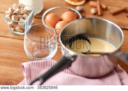 christmas and seasonal drinks concept - pot with eggnog and ladle, glass, ingredients and aromatic spices on wooden background