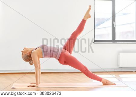 fitness, people and healthy lifestyle concept - young woman doing yoga in upward plank pose with one leg up at studio