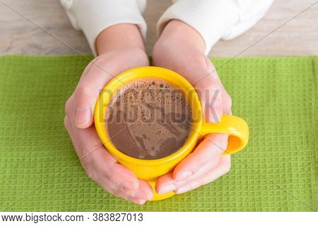 Woman hands holding a cup of hot cocoa or hot chocolate