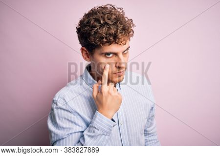Young blond handsome man with curly hair wearing striped shirt over white background Pointing to the eye watching you gesture, suspicious expression