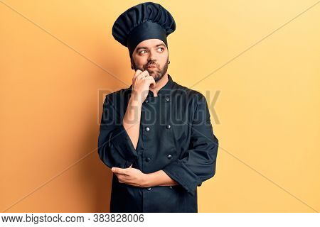 Young hispanic man wearing cooker uniform thinking concentrated about doubt with finger on chin and looking up wondering