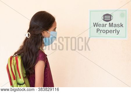 Young Girl Student Adjusting Mask By Seeing Wear Mask Properly Notice On Classroom Wall Before Enter