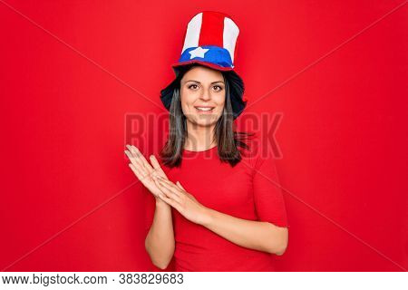 Young beautiful brunette woman wearing united states hat celebrating independence day clapping and applauding happy and joyful, smiling proud hands together