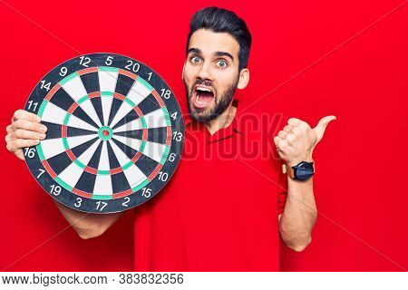 Young handsome man with beard holding dartboard pointing thumb up to the side smiling happy with open mouth