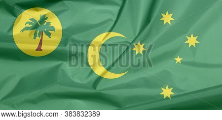Fabric Flag Of Cocos (keeling) Islands. Crease Of Cocos (keeling) Islands Flag Background, A Palm Tr