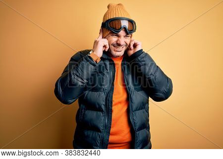 Young handsome skier man skiing wearing snow sportswear using ski goggles covering ears with fingers with annoyed expression for the noise of loud music. Deaf concept.