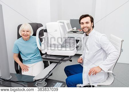 Smiling Optometrist With His Senior Patient, Friendly-looking At Camera, Eye Check-up. Eye Exam And