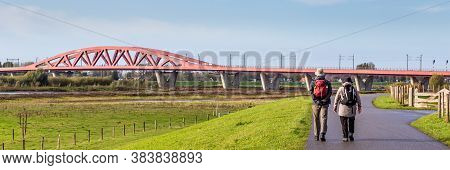 Walking To The Red Railroad Bridge Hanzeboog Over The Ijssel River In Zwolle In The Netherlands