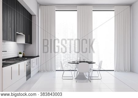 Interior Of Modern Kitchen With White And Black Walls, White Floor, White And Black Cupboards And Di