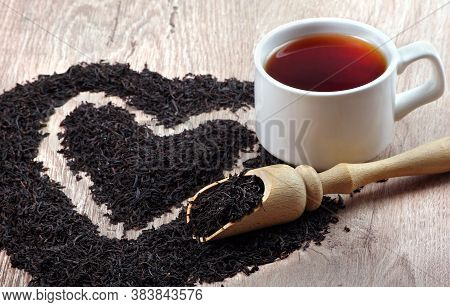 Concept I Like Tea. A Cup Of Black Tea And Dry Black Tea Leaves On A Wooden Table. Heart Symbol Made