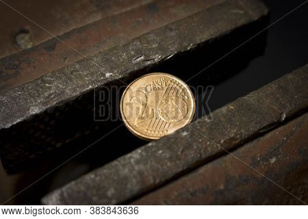 Coin 2 Euro Cents In A Metal Vise. Concept Of Economic Problems. Selective Focus. Close Up