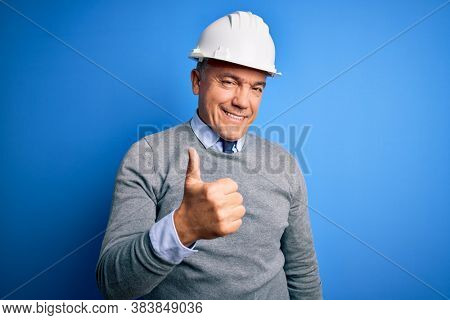 Middle age handsome grey-haired engineer man wearing safety helmet over blue background doing happy thumbs up gesture with hand. Approving expression looking at the camera showing success.