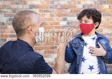 Father And Son Greeting Each Other On The Street. They Are Wearing A Face Mask As A Precaution For T