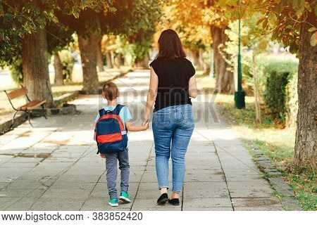 Mother Taking Child To School. First Day At School. Mother Leads A Little School Boy In First Grade.