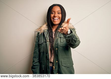 Young african american woman wearing winter parka coat over isolated background smiling friendly offering handshake as greeting and welcoming. Successful business.