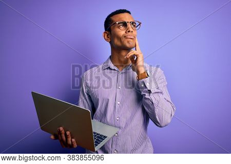 Young handsome african american business man working using laptop over purple background serious face thinking about question, very confused idea