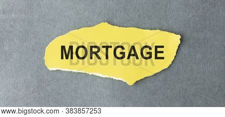 Mortgage Concept. The Word Mortgage On A Piece Of Paper On A Wooden Background.