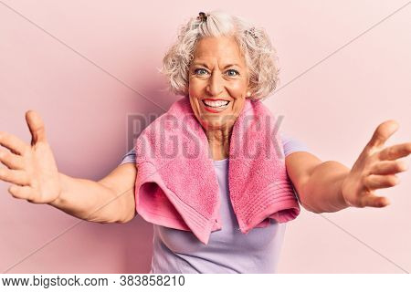 Senior grey-haired woman wearing sportswear and towel looking at the camera smiling with open arms for hug. cheerful expression embracing happiness.