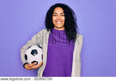 African american curly player woman playing soccer holding football bal over purple background with a happy face standing and smiling with a confident smile showing teeth