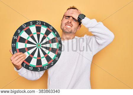 Young handsome man with blue eyes holding dartboard over isolated yellow background stressed with hand on head, shocked with shame and surprise face, angry and frustrated. Fear and upset for mistake.