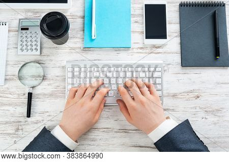 Businessman Hands Working At Vintage Wooden Desk. Office Workspace With Computer Keyboard And Suppli