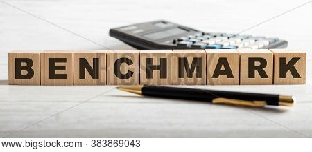 The Word Benchmark Is Written On Wooden Cubes Near A Calculator And A Pen On A Light Background. Bus
