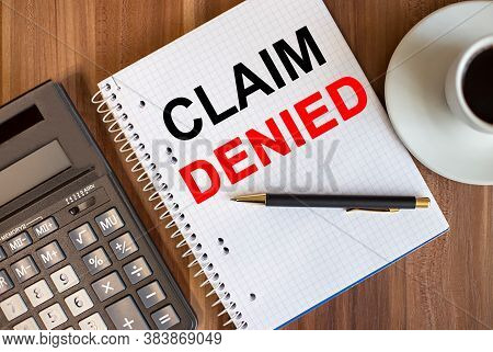 Claim Denied Written In A White Notebook Near A Pen, Calculator And A Cup Of Coffee On A Wooden Back