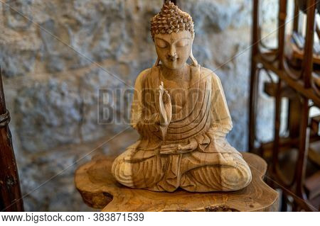 The Beautiful Sculptured Wooden Statue Of Buddha Sitting In Meditation With Closed Eyes On The Lotus