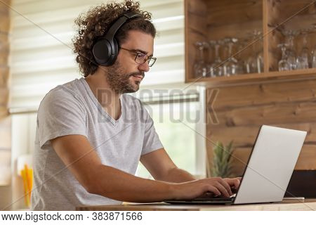 Young Man Sitting At Kitchen Counter, Wearing A Headset And Working On Laptop Computer, Telecommutin