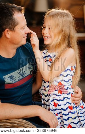 Dad Is Having Fun With A Cute Blonde Daughter. Happy Family. Games With Children After Work. Attenti