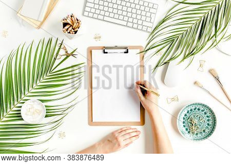 Female Workspace With Female Hands, Clipboard, Tropical Palm Leaves, Computer, Accessories On White