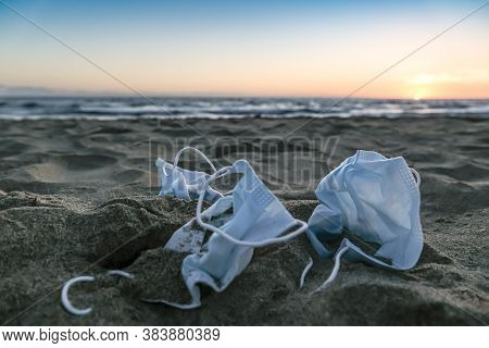 Medical Face Masks Discarded On Sea Coast Over Sunset Background, Covid19 Pandemic Disease Pollution