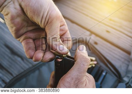 View Of Male Hands Loading A Gun Cartridge With Bullets - Dirty Hands - Daylight - Handgun