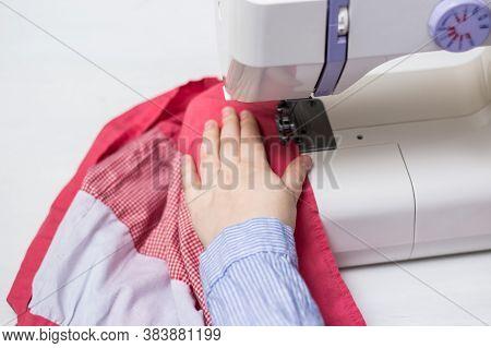 Girl Sews On A Sewing Machine. Modern White Sewing Machine. White And Pink Fabric. Sewing Content.