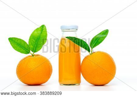 Orange Juice In Glass Bottles With Two Oranges And Leaf On White Background.