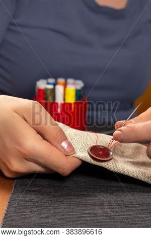 Repair Of Clothes. Sewing On A Torn Button With A Needle And Thread.