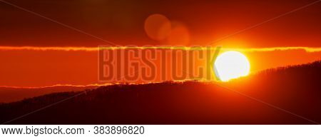 Amazing Sunrise In Mountains, Sunny Disk Rises From Tops Of Hill. Natural Lens Flare In Sky, Sunbeam